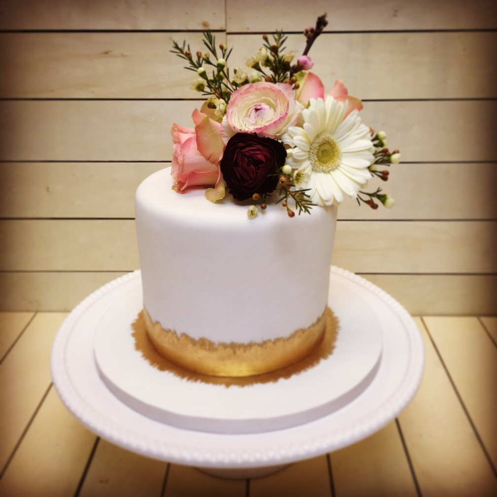 Fresh flowers with gold cake